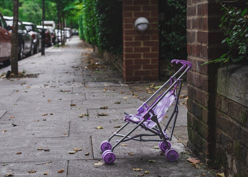 A purple stroller without a child on a sidewalk.