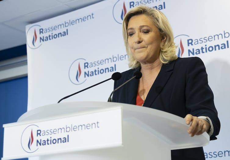 ar-right Rassemblement National (RN) party president Marine Le Pen standing at a podium makes a statement about the election, June2021