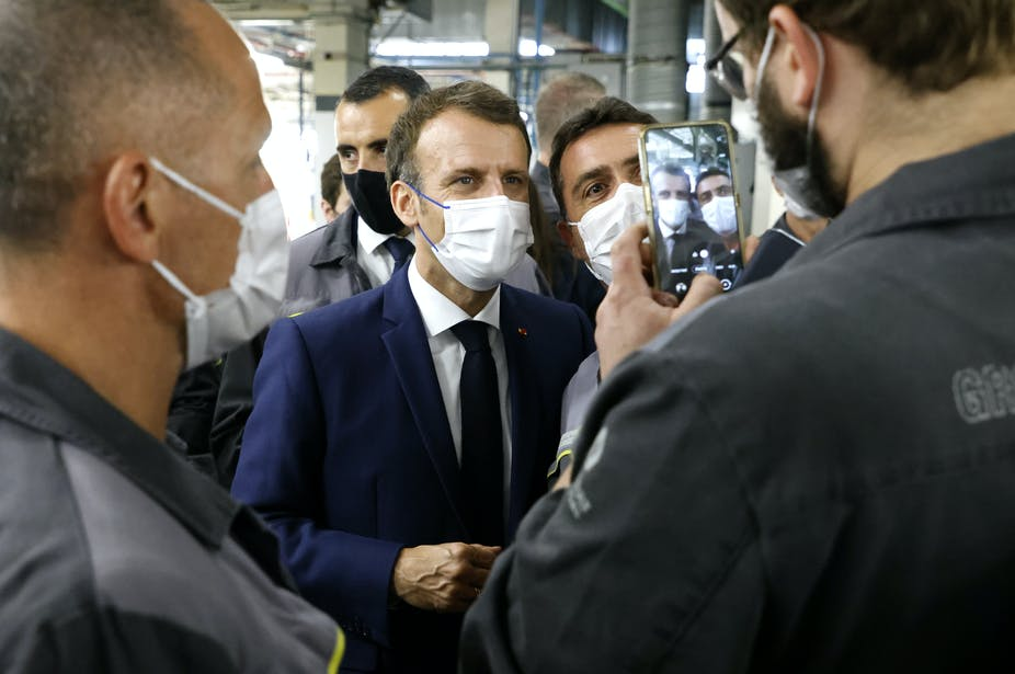 French President Emmanuel Macron poses for a selfie during his visit to the site of the future factory of Japan-based battery maker Envision AESC group, June 2021.