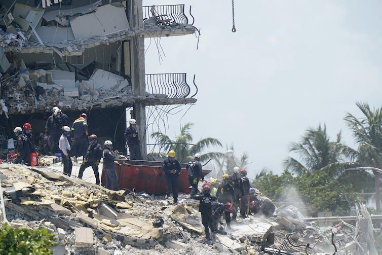 Emergency crews climbing over rubble.