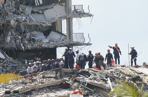 Rescue workers standing on rubble.