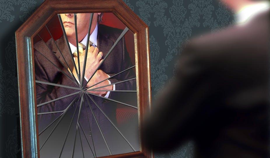 A man adjusts his tie in a broken mirror.