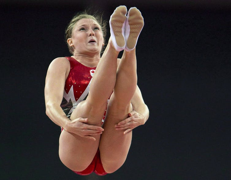 Trampoline athlete Rosie MacLennan grips her thighs during a jump in her routine