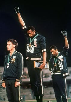 Two athletes with fists raised in protest standing on Olympic podium.