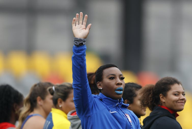 Athlete with raised arm waving at crowd.