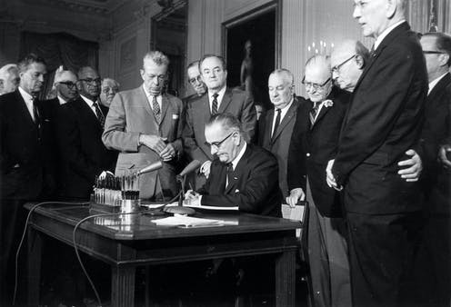 President Lyndon Johnson at a desk, surrounded by white lawmakers, as he signed the 1964 Civil Rights Act with multiple pens.