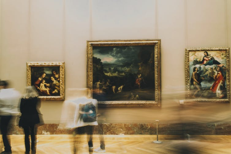 People walk past paintings in a museum.
