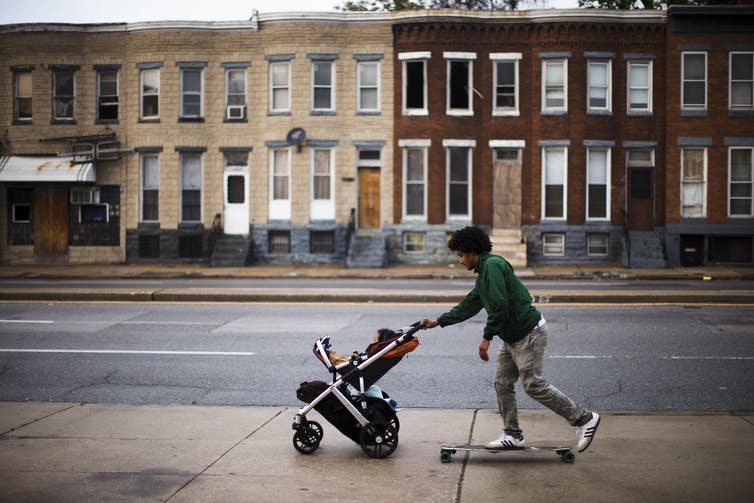 A young Black man on a skateboard pushes his son in a stroller on a sidewalk past blighted buildings in Baltimore.