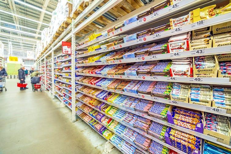 Une allée de supermarché avec plusieurs tablettes de chocolats