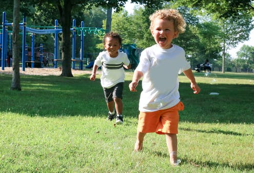 Two young children run outside near a playground.