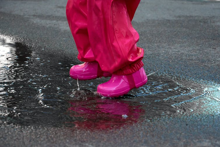 A child's feet in a rainsuit and rainboots jump in a puddle.