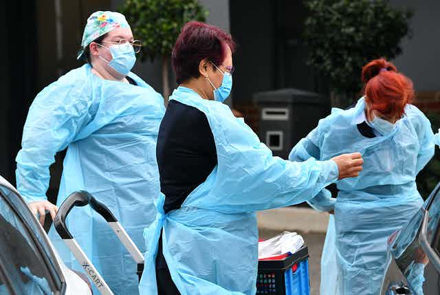 Aged-care workers put on PPE.
