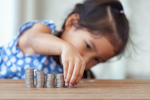 Child stacking coins in different-sized columns