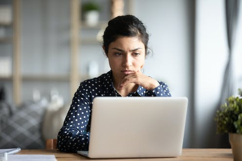 Young woman sitting at a table looks at a computer screen with a concerned expression.