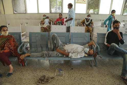 Indian man in mask lying on chairs in hospital.