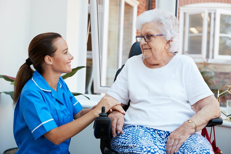 An aged-care worker with an elderly woman.