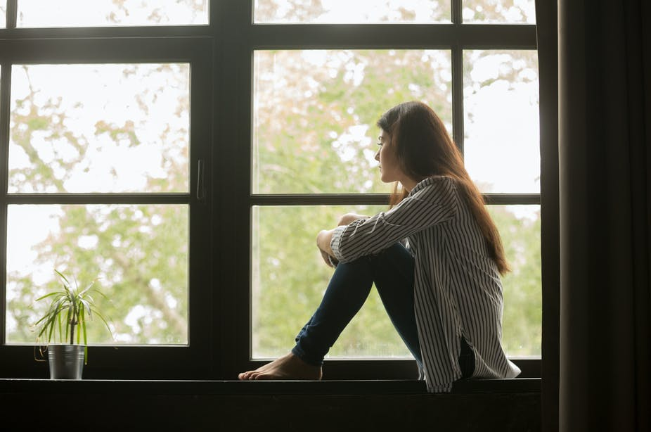 Una mujer se sienta frente a una mujer, mirando con tristeza.