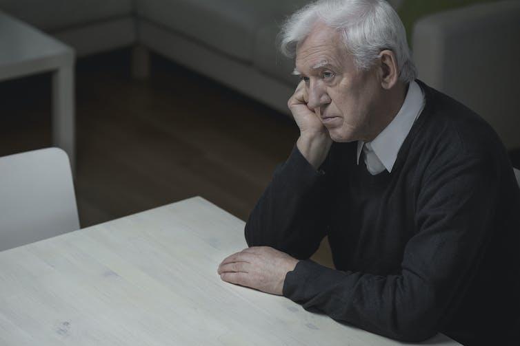 Anciano sentado en una mesa, con aspecto cansado y deprimido.