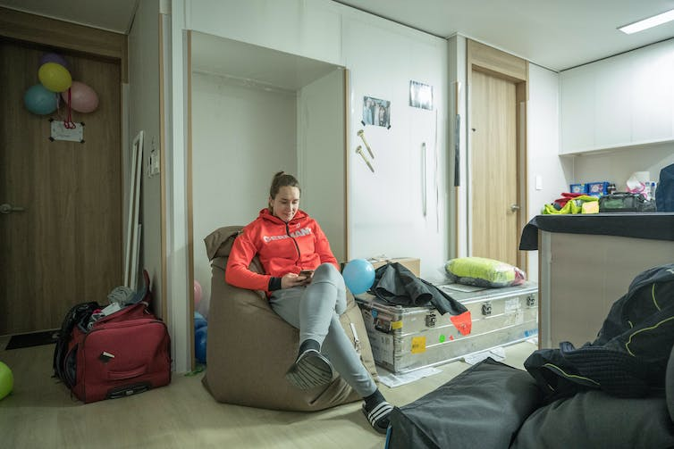 A girl in a red hoodie sits on a giant beanbag in a small hotel room minimally decorated with balloons