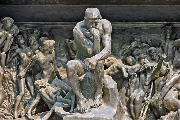 Statue of man thinking surrounded by an orgy of other people.