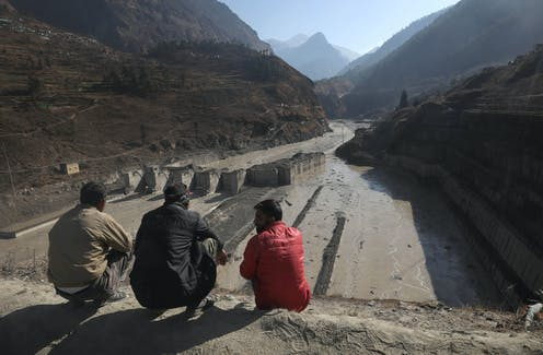 Three men sit on a rise overlooking a damaged hydropower project.