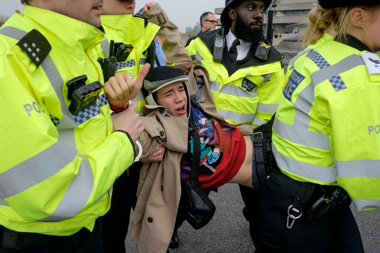 A protester being carried by police