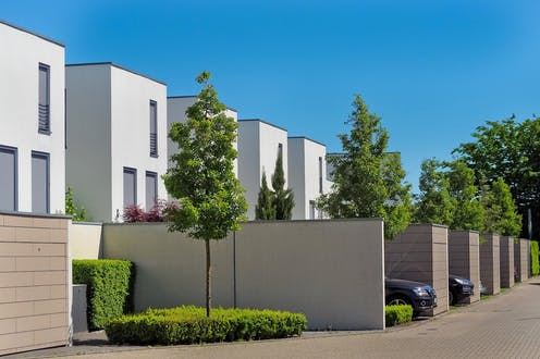 Rows of identical white houses with cars and trees outside