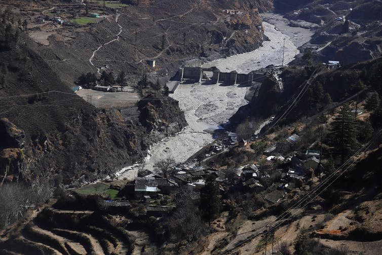 Aerial view of a damaged dam in a mountain valley.