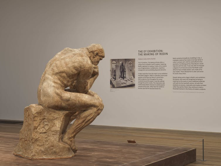 The Thinker statue in a gallery space.