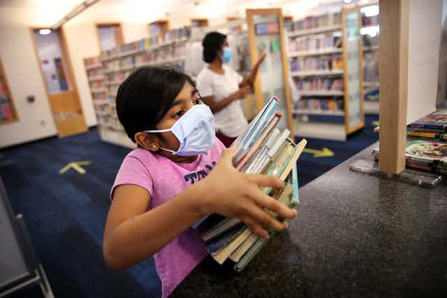 Girls wearing mask holds stack of books
