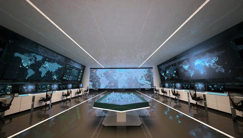 An empty control room with three large screens and a holographic table