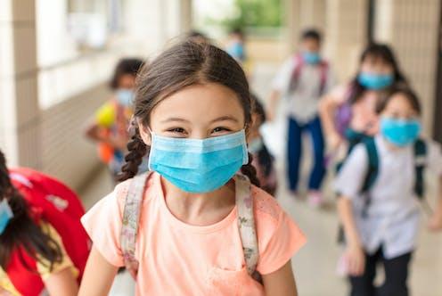 Alumnos de colegio con mascarillas, con una niña sonriente en primer plano.