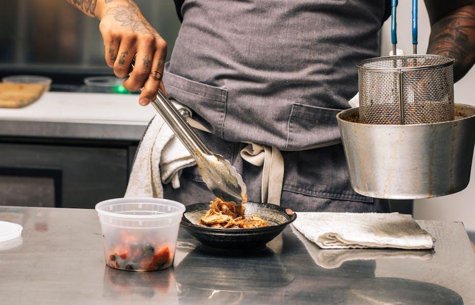 Man puts food in a bowl using tongs.