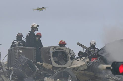 a drone flies above five people in helmets standing on a pile of metal and concrete rubble