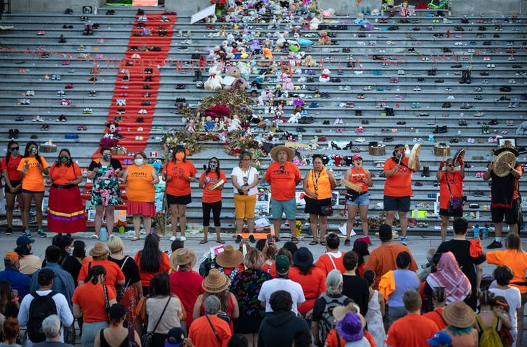 Group of people wearing orange stand in front of steps covered with childrens shoes