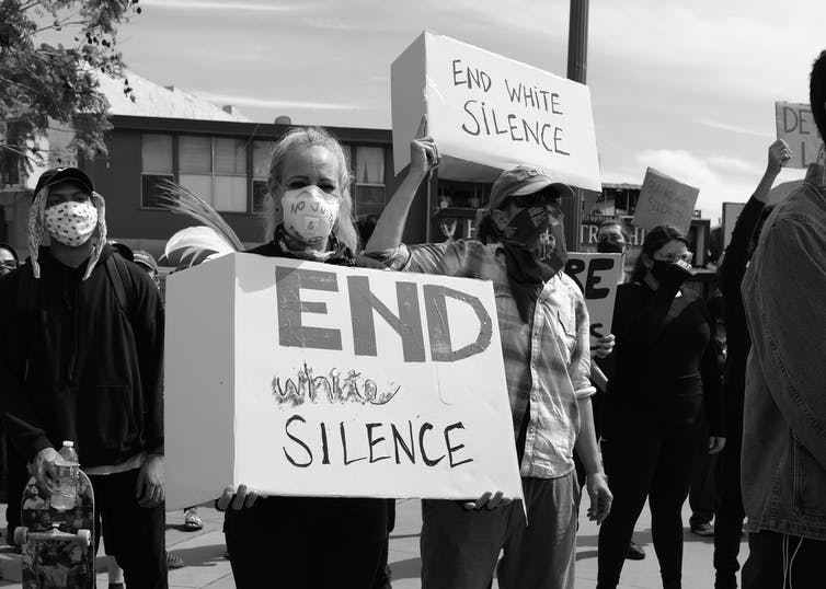 Woman holds a sign that reads 'end white silence'