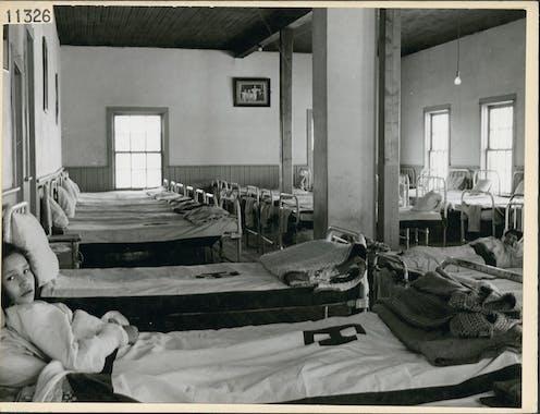 Deux filles sont couchées sur des lits de dortoir dans un pensionnat autochtone.