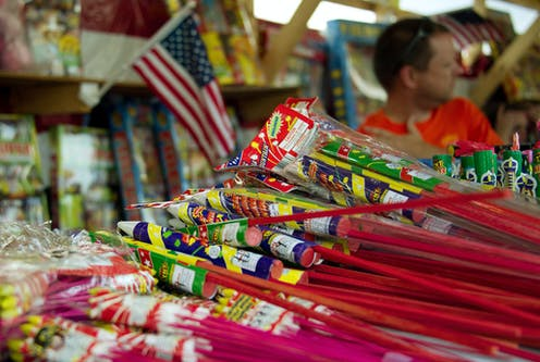 A man sits near a stack of bottle rockets with a flag in the background.