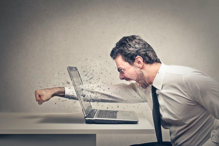Man punches through laptop screen.