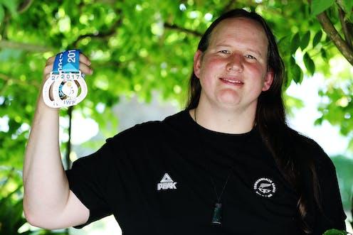 Laurel Hubbard holding up medals