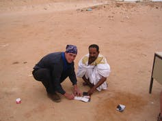 Two people kneeling in the sand over a piece of paper.