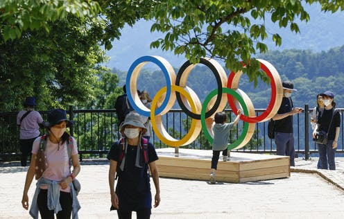 Two tourists wearing masks in front of Olympic Rings