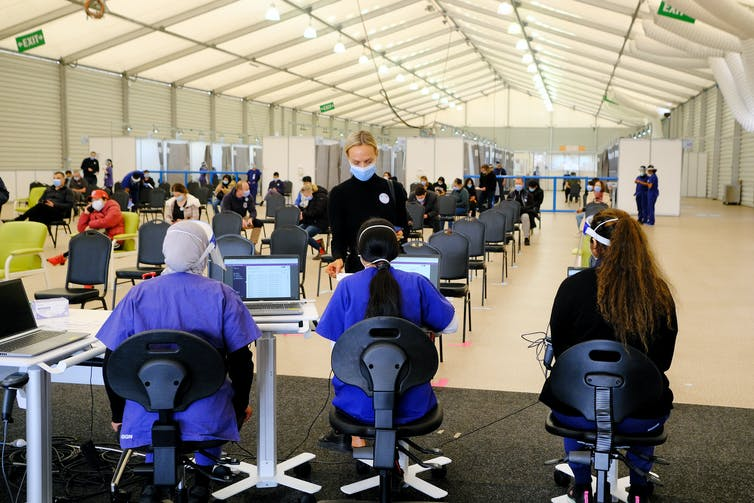 Workers at a mass vaccination hub sit in chairs with their back to the camera.