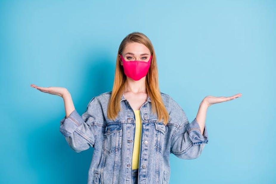 Wanita muda mengenakan topeng dengan tangan di udara, ragu-ragu
