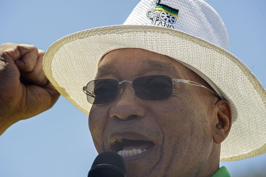 A man speaking intro a microphone, wearing a white hat with an ANC logo on it, and sunglasses