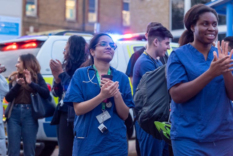 NHS workers gather in crowd and clap