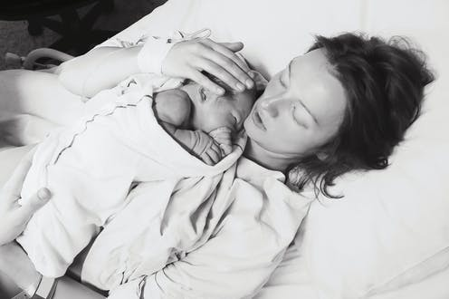 Black and white image of woman lying on a bed with a newborn baby.