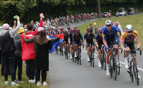 Spectators holding a French flag on the side of the road as the Tour De France riders cycle past