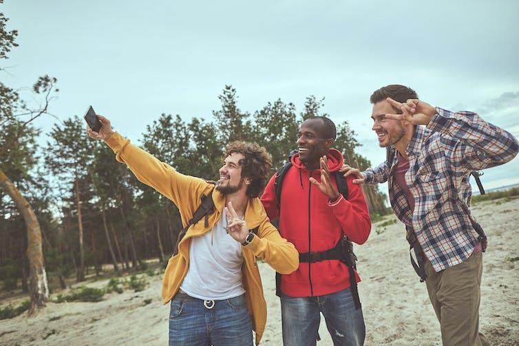 Trois hommes font un égoportrait pendant une randonnée