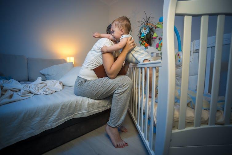 Une femme prend un bébé de son lit, dans un appartement, en pleine nuit